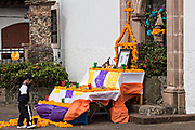 A young Mexican boy views a Day of the Dead altar decorated with marigolds outside the Templo de Nuestra Señora del Sagrario church in Santa Clara del Cobre, Michoacan, Mexico.