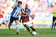 Wigan Athletic defender Harry Maguire battles with Kazenga LuaLua during the Sky Bet Championship match between Wigan Athletic and Brighton and Hove Albion at the DW Stadium, Wigan, England on 18 April 2015.
