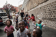 A volunteer is seen playing with Eritrean children in front of Baobab's main gate.