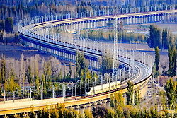 "File photo taken on Nov. 3, 2015 shows a bullet train running through a bridge on the Lanzhou-Xinjiang high-speed railway, northwest China's Xinjiang Uygur Autonomous Region. ""Building more high-speed railways"" has been a hot topic at the annual sessions of China's provincial legislatures and political advisory bodies intensively held in January. China has the world's largest high-speed rail network, with the total operating length reaching 19,000 km by the end of 2015, about 60 percent of the world's total. The expanding high-speed rail network is offering unprecedented convenience and comfort to travelers, and boosting local development as well. Chinese companies have developed world-leading capabilities in building high-speed railways in extreme natural conditions. High-speed railway routes across China have been designed to suit its varying climate and geographical conditions. The Harbin-Dalian high-speed railway travels through areas where the temperature drops to as low as 40 degree Celsius below zero in winter, the Lanzhou-Xinjiang railway passes through the savage Gobi Desert and the Hainan Island railway can withstand a battering from typhoons. The China Railway Corp. plans to spend another 800 billion yuan (around 120 billion U.S. dollars) in 2016, especially in less-developed central and western regions. EXPA Pictures © 2016, PhotoCredit: EXPA/ Photoshot/ Cai Zengle<br />