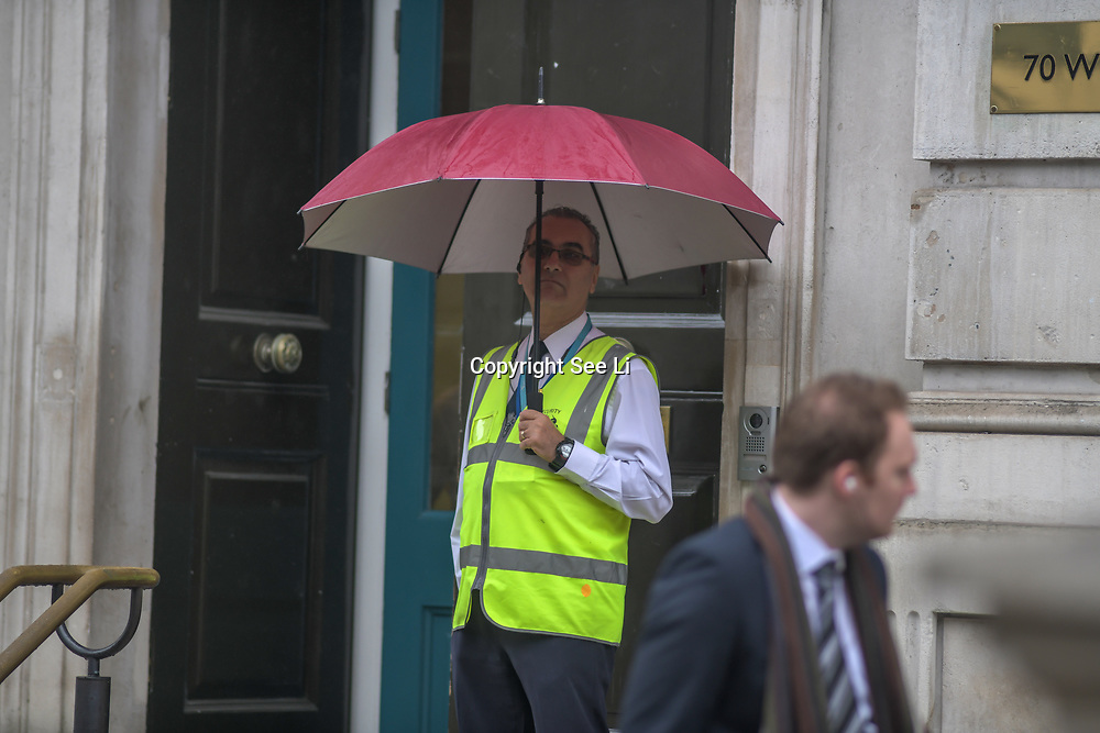 UK Weather:  A security guard holding an umbrella standing in front of 70 Whitehall in Rainy London, UK. 19 July 2019.