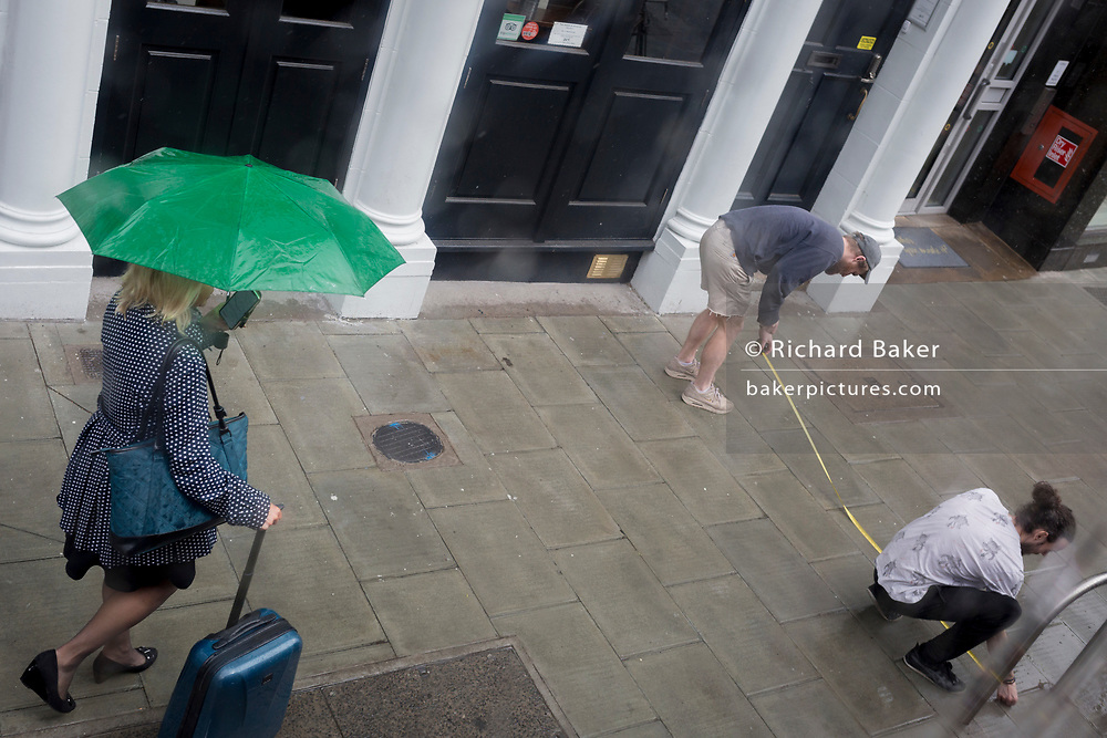 A lady navigating by mobile phone app is distracted while walking towards two men taking measurements using a tape stretched across the pavement in Waterloo SE1, on 9th May 2019, in London, England.
