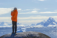 A person enjoying the view and Luigi Peak from Booth Island at Port Charcot in Antarctica.