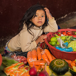 Child helping her mother sell fruits at the fruit market in Chichicastenango, Guatemala.