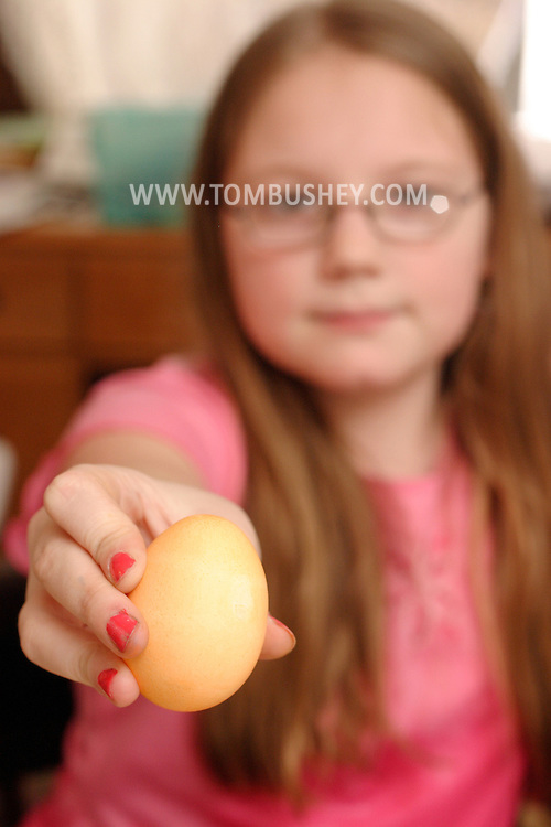 Middletown, N.Y. - A 9-year-old girl holds up an Easter egg she colored on April 15, 2006. ©Tom Bushey/The Image Works.Model release available..Model release available.