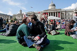 © licensed to London News Pictures. London, UK 21/04/2012. Mary Wright and George Butcher kissing on Trafalgar Square's green ground as the London landmark transformed into an English garden ahead of St George's Day. Photo credit: Tolga Akmen/LNP