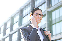 Low angle view of businesswoman using cell phone outside office building