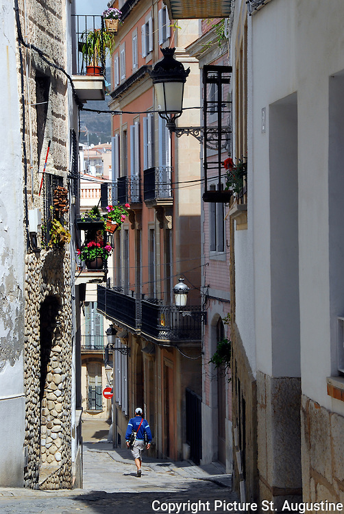 On a sunny spring day a person walks down a narrow street in Stiges, Spain.