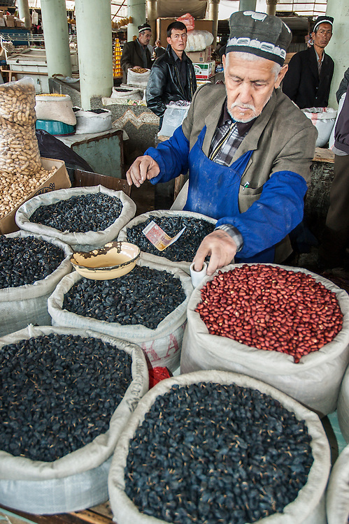 Portrait of an old Tajik man selling raisins and beans in a market in western Tajikistan
