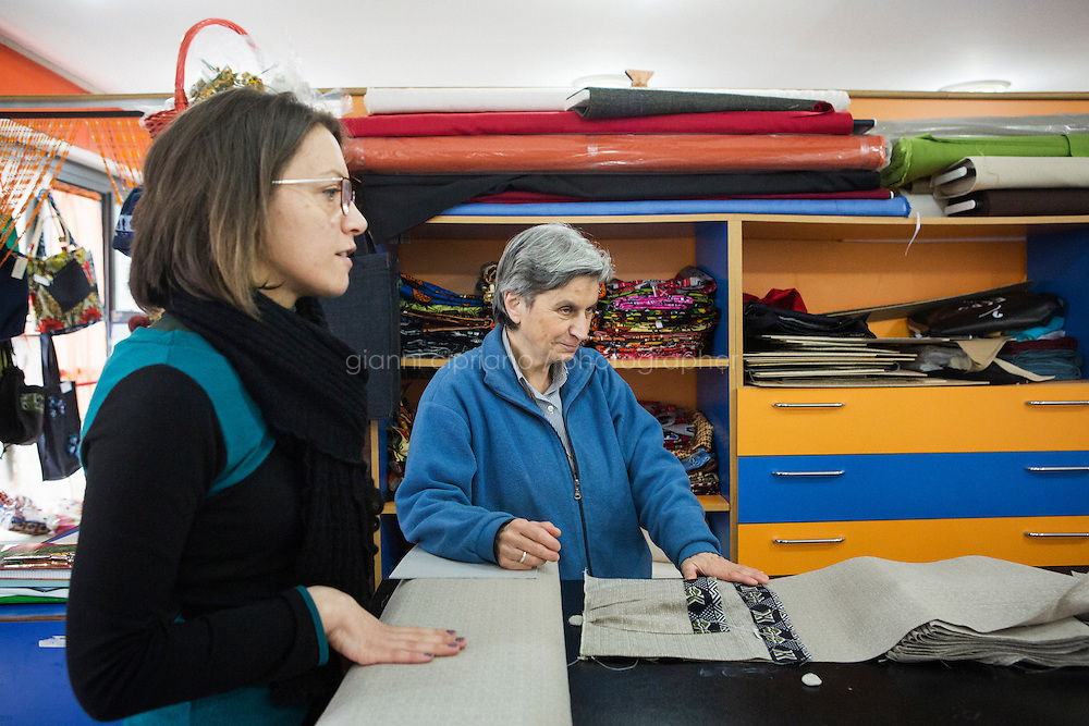 CASERTA, ITALY - 25 FEBRUARY 2015: Sister Rita Giaretta (center), founder of Casa Rut and of the New Hope tailor's shop, listens to a young immigrant woman at the tailoring studio in Caserta, Italy, on February 25th 2015.<br /> <br /> New Hope is an ethnic tailor's shop that makes a variety of colourful products working mainly african fabrics. The New Hope social cooperative, founded in 2014, promotes a training workshop for your immigrant women, many of which have children, that want to integrate in Italian society.