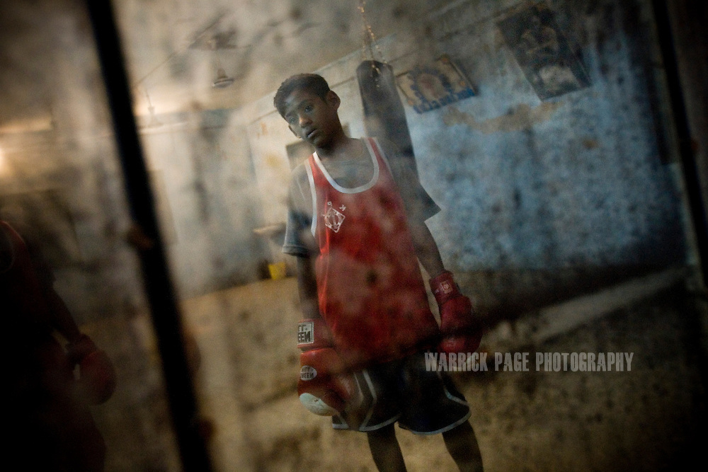 KARACHI, PAKISTAN - OCTOBER 12: A members of the Young Baloch Boxing Club is see in a reflection of a mirror as he prepares for training, Sunday, October 12, 2008, in Karachi, Pakistan. Lyari is Karachi's poorest, most dangerous, drug and crime-infested slum, but has produced the bulk of Pakistan's champion boxers. Boxing has been a way of survival for many of the young men, who are often sponsored by corporations and event the military, to box for them at events throughout the city and the country. Lacking in the most basic resources, including a sufficient diet, the young boxers have watched countless champions on television throughout the years, attempting to emulate their abilities. (Photo by Warrick Page)