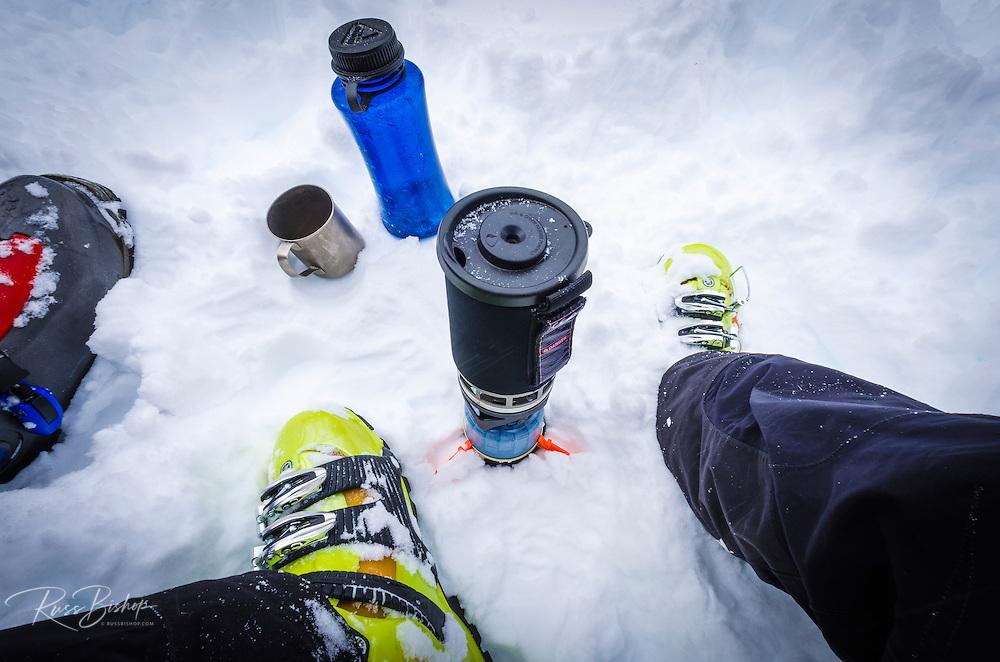 Backcountry skier fixing a hot drink, John Muir Wilderness, Sierra Nevada Mountains, California  USA