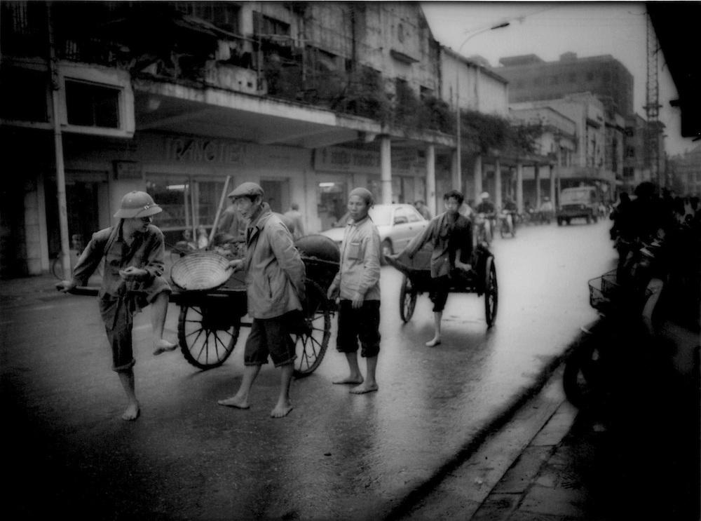 Barefoot workers leading carts through Hanoi, Vietnam.