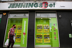 © Licensed to London News Pictures. 14/06/2020. London, UK. A man wearing a face covering walks past a branch of Jennings Bet in north London, which will reopen on 15 June as coronavirus lockdown restrictions are eased. The government has announced that all betting shops can re-open on Monday 15 June. Betting shops were closed late March following outbreak of COVID-19. Photo credit: Dinendra Haria/LNP