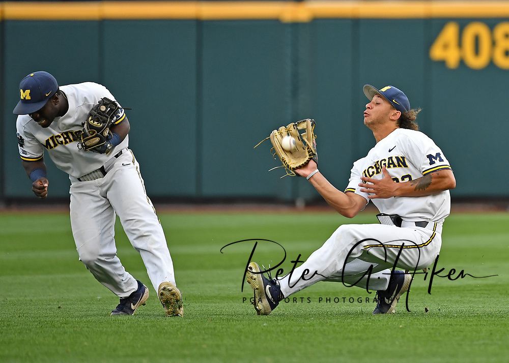 Jordan Brewer #22 of the  Michigan Wolverines makes a sliding catch behind Ako Thomas #4 in the second inning against the Vanderbilt Commodores during game two of the College World Series Championship Series on June 25, 2019 at TD Ameritrade Park Omaha in Omaha, Nebraska.