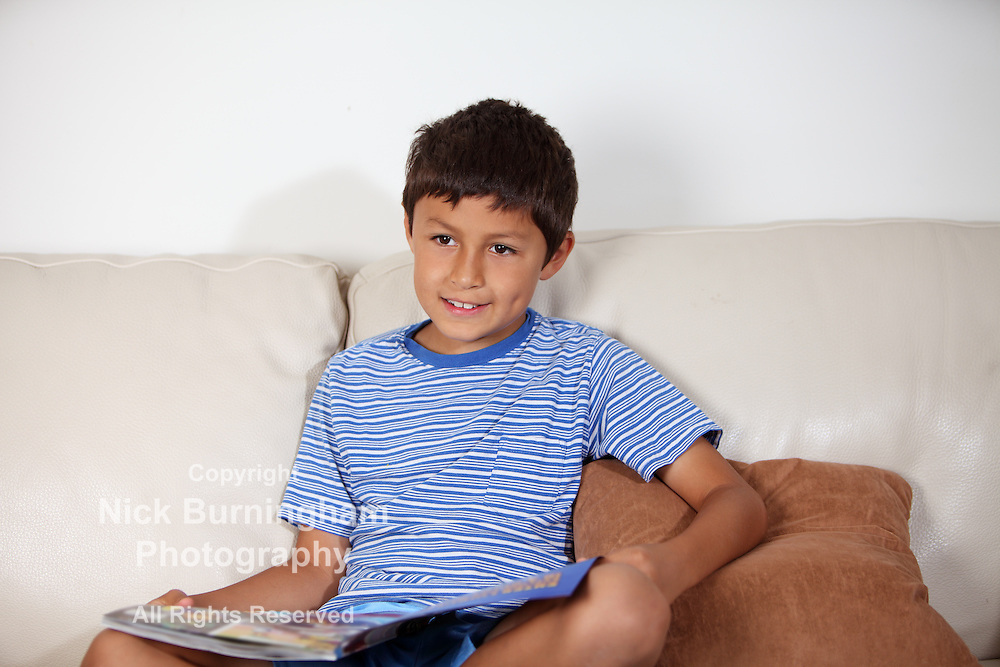 Young boy on the sofa reading a magazine