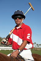 Polo Player holding polo stick on horseback on polo field