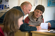 A teacher giving advise to a pupil at the Moray Rudolf Steiner School, Forres, Scotland during a class. The school was established in 1986 and founded on the principles of Austrian philosopher Rudolf Steiner (1861-1925) who established a network of schools based on his teachings which has spread to around 60 countries worldwide. The first of over 1000 of Steiner's Waldorf schools was founded in 1919 in Stuttgart, Germany and became one of the world's largest independent educational systems.
