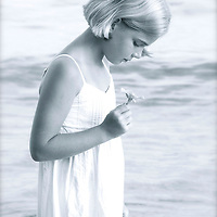 A young girl with blonde hair looking down wearing a white summer dress holding a single flower standing beside a lake