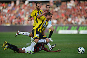 10.03.2013 Sydney, Australia. Wellingtons defender Ben Sigmund brings down Wanderers Dutch midfielder Youssouf Hersi during the Hyundai A League game between Western Sydney Wanderers and Wellington Phoenix FC from the Parramatta Stadium. The Wanderers won 2-1.