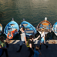 Italy, La Spezie, Line of tourists walks past wooden fishing boats tied up at Cinque Terre village of Vernazza along Mediterranean Coast on spring afternoon.