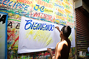 CARTAGENA, COLOMBIA - June 3, 2015: In the middle of Bazurto Market, a young man paints signs for upcoming Champeta parties at local clubs.<br />