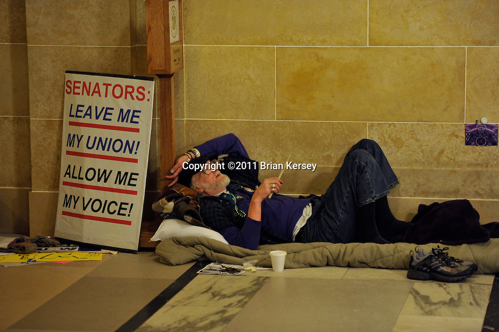 Protester Dennis Lyebhaber rests at the state capitol in Madison, Wisconsin on February 23, 2011. Twenty- four hour demonstrations have been taking place for nearly two weeks as the legislature considers the budget proposed by Republican Gov. Scott Walker, which  includes cuts in benefits for state workers and takes away many of their collective bargaining rights.      (Photo by Brian Kersey)