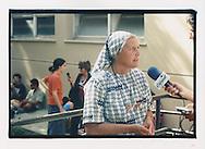 """Proteste contro il summit del G8, Genova luglio 2001. Media center del GSF presso la scuola Pertini, via Battisti, 16 luglio. Suora intervistata da giornalista. Al """"Patto di lavoro"""" del Genoa Social Forum aderiscono 1187 associazioni di svariati orientamenti politici e culturali, incluse associazioni religiose."""