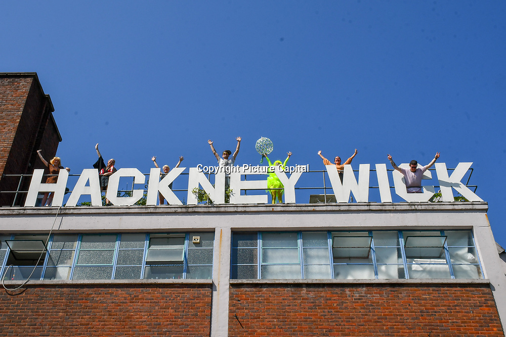London, England, UK. 23 July 2019: Artists embrace with Mai Nguyen Tri of the Holly Wick sign in preparation for Hackney WickED Open Studios and open its door to public on Hackney Wicked DIY Open Studios Friday 26 July-Sunday 28 July, London, UK.