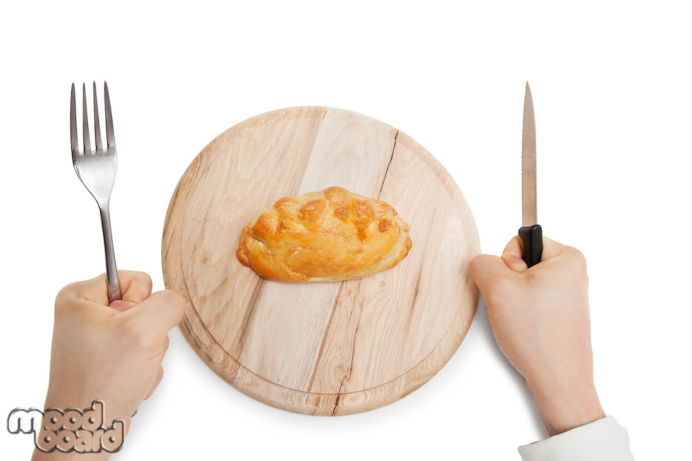 Hands holding knife and fork with Cornish pastry on wooden plate over white background