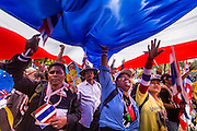 "09 DECEMBER 2013 - BANGKOK, THAILAND: Thai anti-government protestors walk to Government House under a Thai flag in Bangkok. Thai Prime Minister Yingluck Shinawatra announced she would dissolve the lower house of the Parliament and call new elections in the face of ongoing anti-government protests in Bangkok. Hundreds of thousands of people flocked to Government House, the office of the Prime Minister, Monday to celebrate the collapse of the government after Yingluck made her announcement. Former Deputy Prime Minister Suthep Thaugsuban, the organizer of the protests, said the protests would continue until the ""Thaksin influence is uprooted from Thailand."" There were no reports of violence in the protests Monday.      PHOTO BY JACK KURTZ"