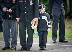 © licensed to London News Pictures. 08/09/2011. Brize Norton, UK..A young boy wearing a military hat watches The Body of Sergeant Barry Weston of 42 Commando Royal Marines passes the memorial in Carterton after arriving at RAF Brize Norton for the first time. Sgt Weston was killed on August 30 while leading a patrol near the village of Sukmanda in southern Nahr-e Saraj, Helmand province. Photo credit: Ben Cawthra/LNP