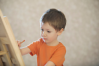 A young boy drawing onto a canvas