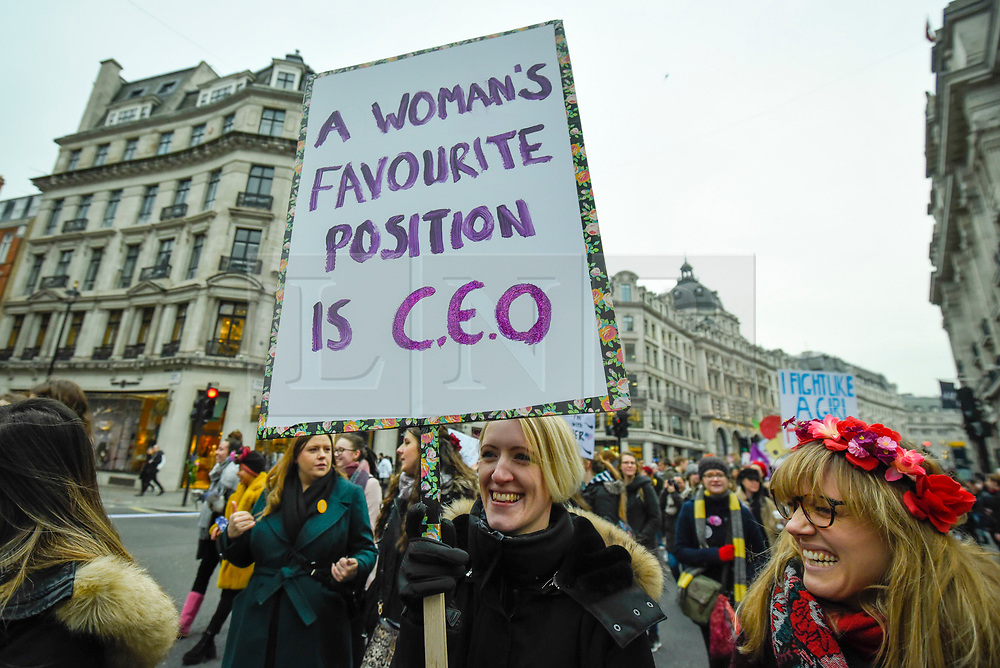 "© Licensed to London News Pictures. 19/01/2019. LONDON, UK. A woman holds up a sign as thousands of participants take part in the Women's March in the capital, one of 30 such worldwide marches protesting against violence against women and the negative impact of austerity policies.  London's theme this year is ""Bread and Roses"", honouring Polish-American suffragette Rose Schneiderman who, in 1911 said ""The worker must have bread but she must have roses too"", in response to a factory fire where 146 mainly female garment workers died.  Photo credit: Stephen Chung/LNP"