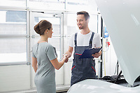 Smiling maintenance engineer shaking hands with female customer in car repair shop