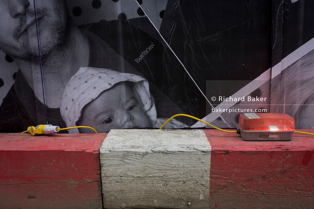 A baby's face on a construction site hoarding peers over the top of a timber traffic barrier and wiring.