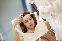 Lady looking at a white bra  with other white bras hanging up