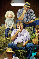 Jeff Sackmann and his son Trevor Sackmann, 2, from Warden, Wash.sit at the top of the hay bale bleachers while bidders wait for the action to commence at a production cattle sale held Friday, Sept. 23, 2011 at the Rocking R Ranch in Hayden, Idaho.