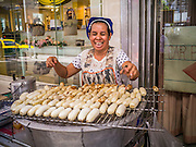 "04 OCTOBER 2012 - BANGKOK, THAILAND: A grilled banana vendor works on Sukhumvit Road near Soi 24 in Bangkok, Thailand. Thailand in general, and Bangkok in particular, has a vibrant tradition of street food and ""eating on the run."" In recent years, Bangkok's street food has become something of an international landmark and is being written about in glossy travel magazines and in the pages of the New York Times.       PHOTO BY JACK KURTZ"