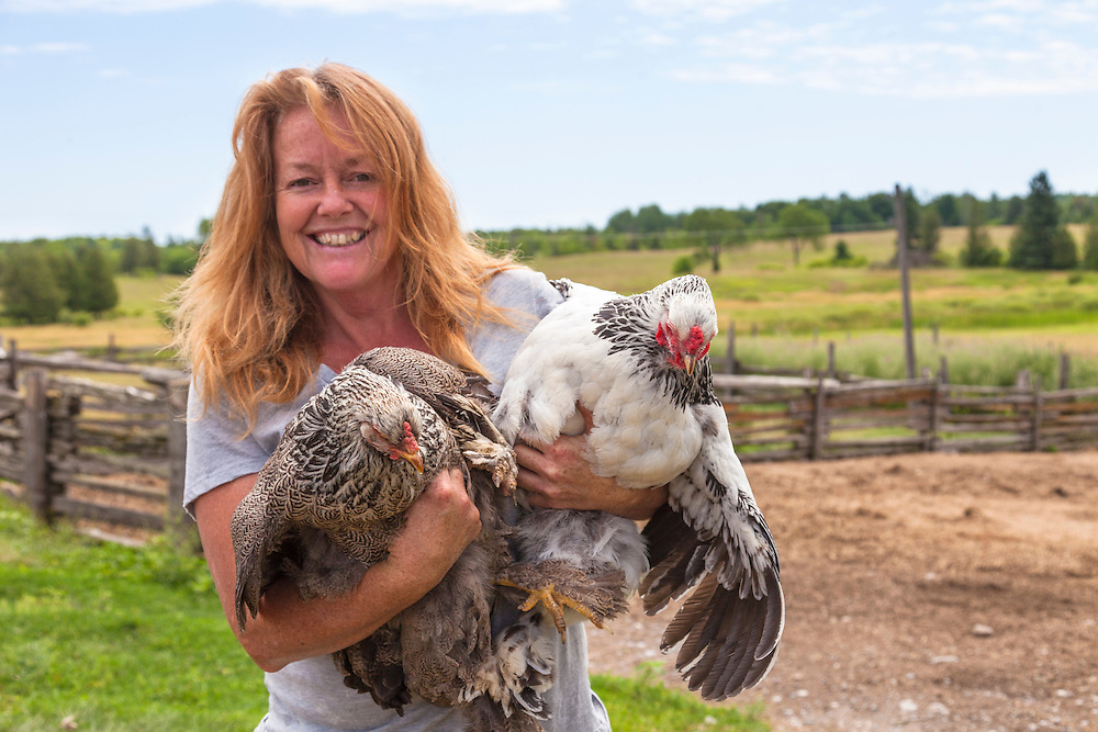 Heritage breed farmer Monana Jones of Wholearth Farmstudio holds 2 heritage breed chickens, a Dark Brahma hen and a Light Brahma hen.