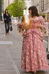 A lady wearing a formal gown is carrying a large gold egg, Seattle, WA, USA
