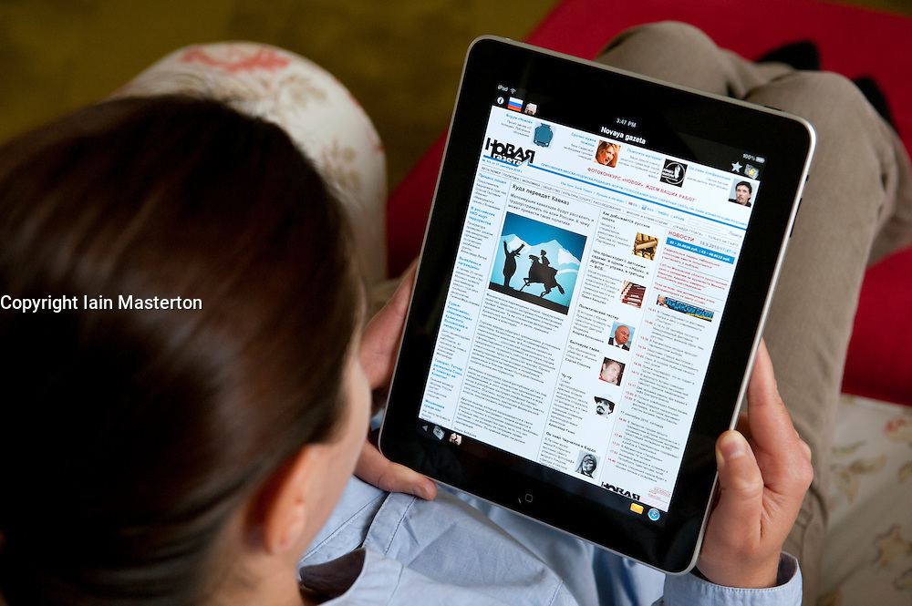 Woman using iPad tablet computer at home to read Russian Novaya Gazeta newspaper