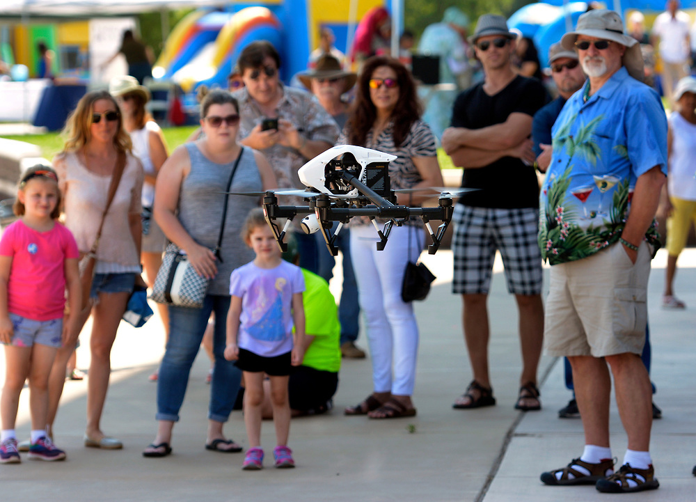 gbs062517c/ASEC - An EJI Inspire drone lands on the sidewalk as a crowd watches at the Colibri Media House booth at the Drone Discovery Day at the Anderson Abruzzo Albuquerque International Balloon Museum on Sunday, June 25, 2017. (Greg Sorber/Albuquerque Journal)