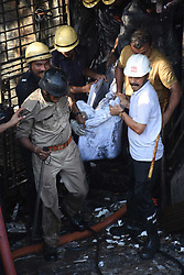 May 24, 2019, Gujarat, India: Rescuers carry the body of victim out of a building in Surat town of the western Indian state of Gujarat. The death toll in a major fire incident in India's western state of Gujarat has risen to 18, and five injured have been admitted to a hospital, a senior Fire Department official confirmed to Xinhua over phone on Friday..   The fire broken out inside a four-storey building in Gujarat's Surat town on Friday afternoon. (Credit Image: © Stringer/Xinhua via ZUMA Wire)