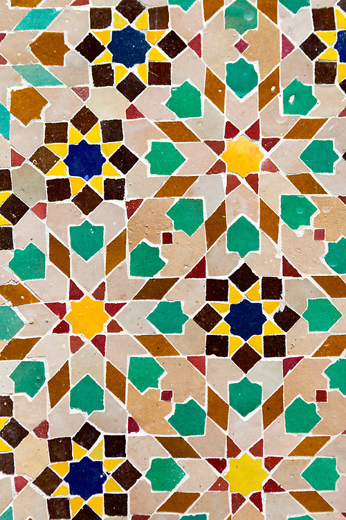 Zellige mosaic work - Islamic, geometric mosaic patterns - line the walls around a doorway in the Marrakesh Medina, Morocco