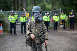 © licensed to London News Pictures. London, UK 03/08/2013. A child protester staining outside the entrance of Cuadrilla's drilling site in Belcombe with a gas mask to protest against the drilling. A protest against oil exploration in Balcombe, West Sussex enters its 10th day on Saturday, August 03, 2013, a day after energy company Cuadrilla began drilling at the site. Photo credit: Tolga Akmen/LNP