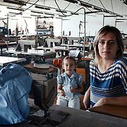 Silvana Romano 38 anni, operaia della fabbrica Tacconi Sud di Latina, all'interno del capannone della fabbrica tessile occupata, seduta al tavolo da lavoro con la figlia Gaia di 3 anni. Silvana è operaia specializzata addetta alla macchina da cucire e all' incollaggio e raspatura dei tessuti gommati. L'occupazione e' iniziata il 19 gennaio 2011 a seguito della comunicazione del licenziamento di tutti i dipendenti. La produzione dell'impianto e' ferma e l'intento delle donne e' quello di salvaguardare i materiali ancora al suo interno e di chiedere garanzie per il loro futuro lavorativo. Silvana ha lavorato alla Tacconi Sud per 20 anni.