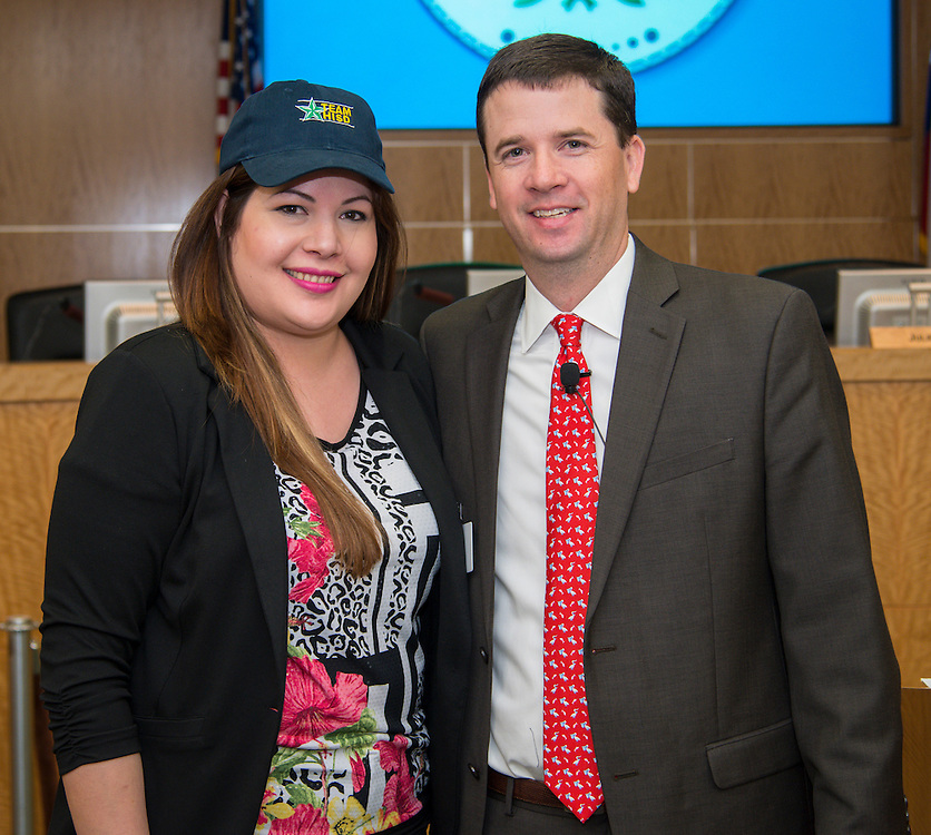 Dr. Andrew Houlihan, right, presents Sanchez Elementary School principal Mayra Ramon, left, with a Team HISD cap, June 11, 2014.