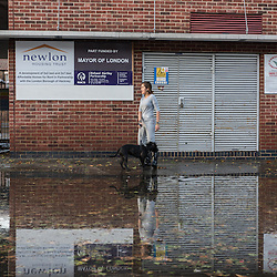 London, UK - 19 September 2014: a woman stands on a flooded street as torrential rains cause floods and travel disruptions in East London