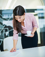 Young businesswoman reading document while holding coffee in office